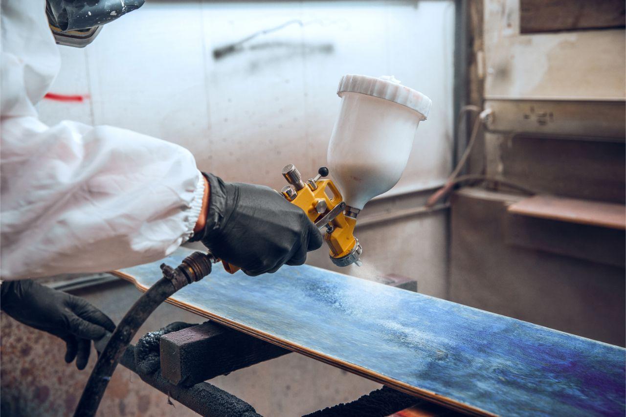A man spraying paint on an aluminum surface